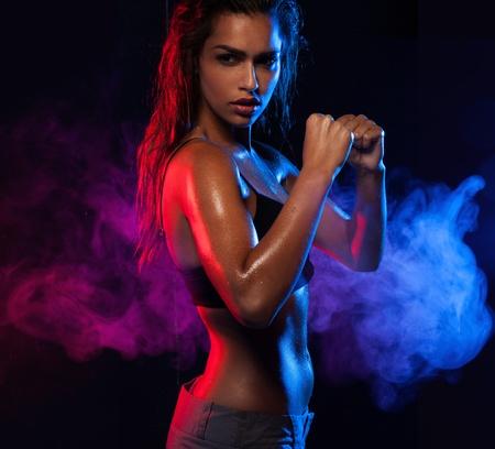 levantar pesas: Decidida mujer sexy en forma de trabajo en el azul y el violeta de antecedentes de onda de humo