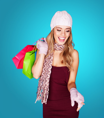 Joyful young woman with shopping bags wearing a trendy cap, scarf, and gloves laughing as she dangles the brightly coloured bags over her shoulder, over blue photo