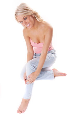 top: Sexy casual blond woman with a lovely warm friendly smile kneeling barefoot on the floor in a stylish summer top and jeans, over white