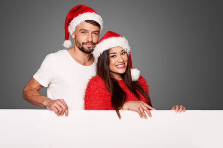 Couple wearing Santa hats holding a blank white billboard on a gray background photo