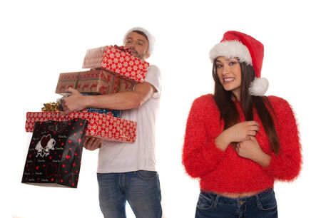 Young couple laden with Christmas presents with the woman standing smiling in the foreground in a festive red Santa Hat while the laughing man holds all the gifts behind her isolated on white Stock Photo - 25853184