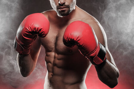 pugilist: Closeup of young boxer wearing red boxing gloves