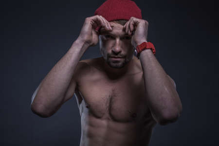 Low key image of a fit shirtless young man wearing a red beanie hat in a black background