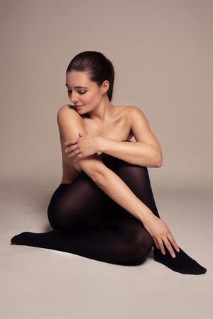Beautiful graceful topless woman in black pantyhose posing sitting on the floor in a sensual pose with a serene smile with her arm hiding her breasts photo