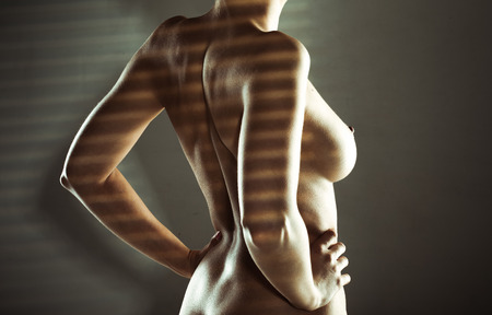 Sexy naked woman standing in striped shadow with her hands on her waist and her naked breast and nipple in profile against the darkness with copyspace photo
