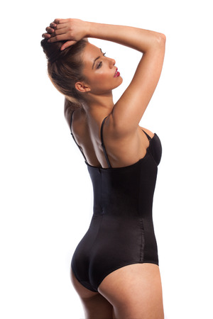 bathing costume: Sensual young woman in a black bathing costume standing with her hands raised to her hair accentuating her curvaceous body, side view isolated on white