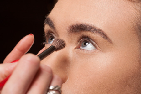 stage make up: Beautician applying cosmetics on a young model using a soft brush to contour under her eyes with powder to give a smooth complexion Stock Photo