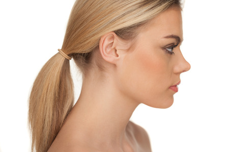 Close-up profile portrait of a beautiful blond woman with serious expression and looking down on a white background