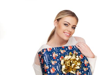 hair wrapped up: Young woman holds a gift wrapped in christmas paper, isolated on white
