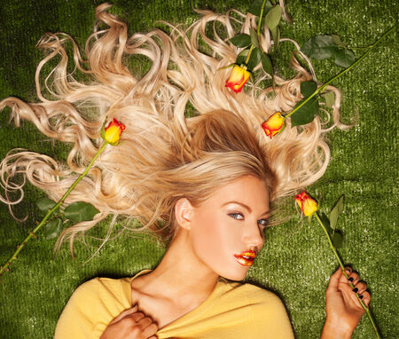 Seductive sexy beautiful blond woman lying looking up at the camera with her hair spread out artistically on a green background covered in roses, overhead view photo