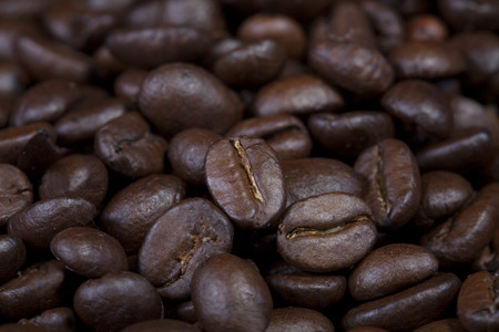 Background texture of dark full roasted coffee beans for grinding to make a brew of strong espresso coffee