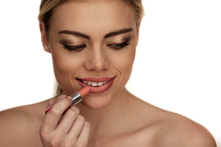 Beautiful young woman applying lipstick on white , smiling photo