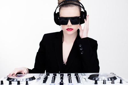 sexy headphones: Beautiful sexy disc jockey at her deck standing over the turntables wearing modern sunglasses and headphones with pouting red lips