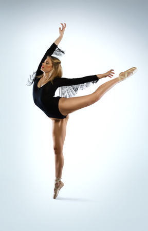 en pointe: Beautiful graceful ballet dancer doing an arabesque en pointe with her arms outspread in an elegant pose