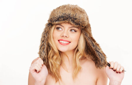 Studio portrait over white of a young, attractive blonde woman, wearing nothing but a fur-lined hat. photo