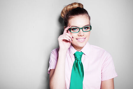 geeky: Beautiful nerdy young woman in glasses and a green tie with her blond hair in a bun smiling at the camera Stock Photo