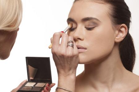 parpados: Esteticista aplicar maquillaje de ojos en los p�rpados de un modelo de joven y atractiva antes de una actuaci�n sesi�n de fotos o de la etapa Foto de archivo
