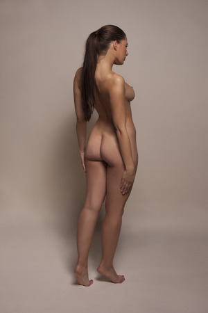 partially nude: Elegant full length nude woman turned partially away from the camera displaying her sexy buttocks with her right breast in profile in a tasteful aesthetic portrait