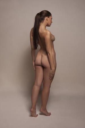 Elegante longitud completa de la mujer desnuda giró parcialmente fuera de la cámara mostrando su sexy nalgas con su pecho derecho en el perfil en un retrato de buen gusto estético Foto de archivo