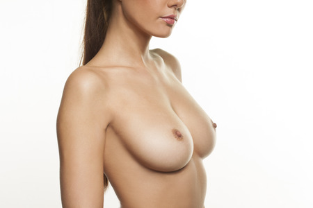 bare breasts: Beautiful bare female breasts and nipples of a young woman posing sideways to the camera isolated on white, close up view