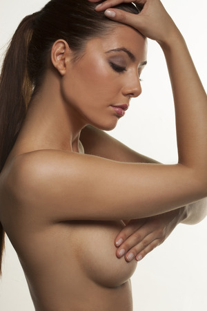 female nudity: Close up sensual portrait of a beautiful naked young woman shielding her nipple with her hand posing sideways with a serene expression and downcast eyes