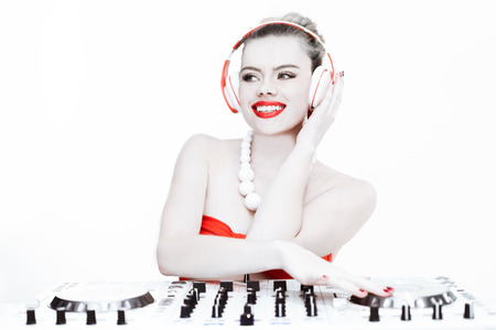 sexy headphones: Sexy happy female DJ listening to headphones while mixing music using the turntable of the sound system, on white background
