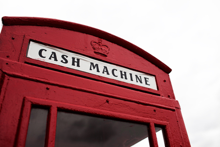 cash machine: Iconic British red telephone booth converted to a cash machine with the sign above the door below the Royal crown Stock Photo