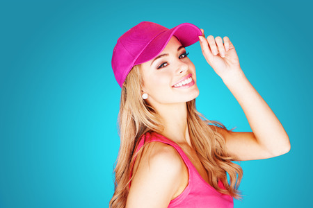 Vivacious beautiful blond woman in summer fashion wearing a trendy pink peak cap and top over a blue background photo
