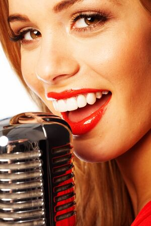 Close up portrait of a beautiful young female vocalist wearing bright red lipstick singing into a microphone