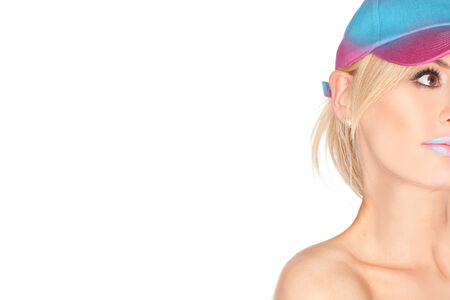Partial portrait of a beautiful blond woman wearing a peaked summer cap looking upwards, one eye visible isolated on white with copyspace photo