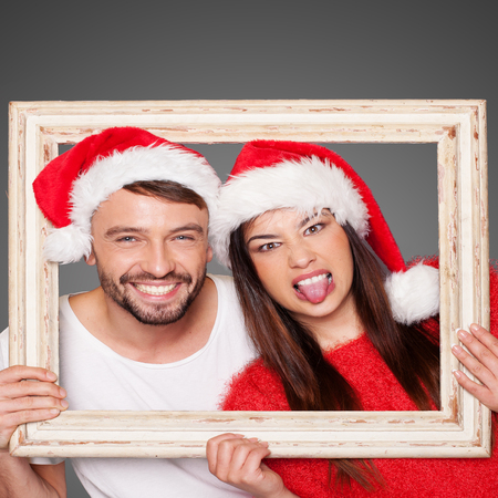Couple looking through and empty picture frame wearing Santa hats with the woman making faces photo