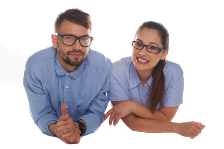 Nerdy looking couple wearing blue shirts and thick frame glasses looking at camera while leaning forward on a white background photo