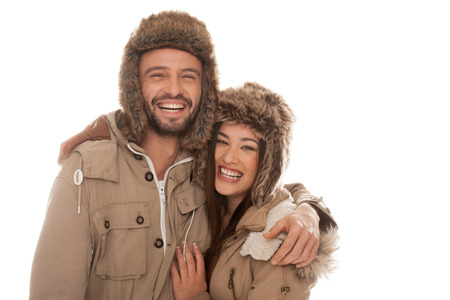winter couple: Laughing vivacious young couple in winter fashion standing side by side with their arms around each other in furry hats and warm jackets isolated on white Stock Photo