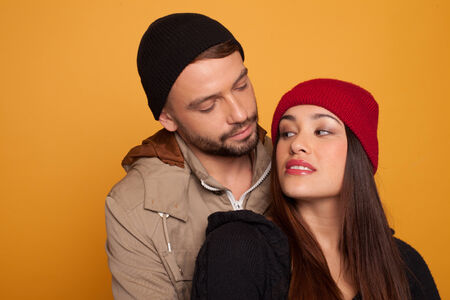 beanies: Beautiful young couple in love standing looking into each others eyes with a look of desire and longing, over an orange studio background