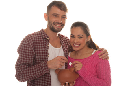 Young couple with their piggy bank standing arm in arm smiling happily as they drop a coin into the slot isolated on white