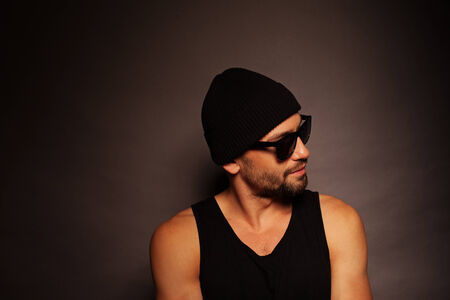 Trendy young man portrait looking away in a dark background wearing a beanie hat, tank top and sunglasses photo