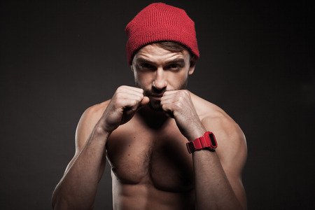 Fit young man in an aggressive pose with raised arms and closed fists ready for fight photo
