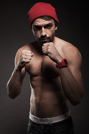 Portrait of a fit young man in an aggressive pose with raised arms and closed fists ready for fight photo