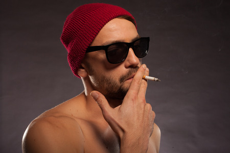 Sexy shirtless bearded man in sunglasses wearing a red knitted beanie cap smoking a cigarette photo