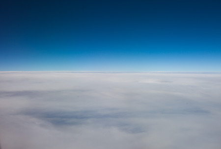 obscuring: Flying above a layer of high altitude cirrostratus cloud forming a hazy white blanket in the blue sky obscuring the earth below