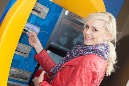 automatic teller machine bank: Smiling attractive young blond woman inserting her card in an ATM at the bank as she prepares to withdraw money Stock Photo