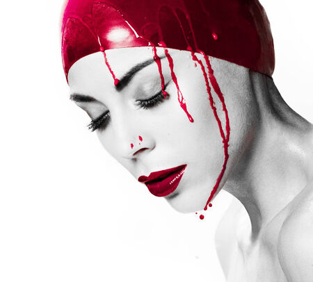 self harm: Dramatic artistic portrait of a bleeding woman with closed eyes and a serene expression wearing a red cap dripping blood with selective colour to the cap, blood and her red lips, isolated on white