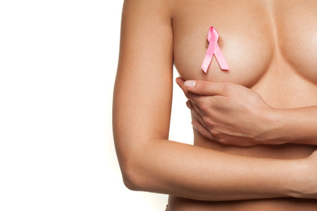 seni: Nudo di donna che indossa un nastro rosa cancro al seno attaccato al capezzolo nudo come lei coppe il seno con la mano in un movimento aggraziato, isolato su bianco