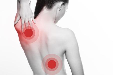 artrosis: Vista desde detrás de una mujer joven con el hombro y el dolor de espalda que se remonta a la mano para tocarle el omóplato con el color rojo selectivo a las áreas lesionadas