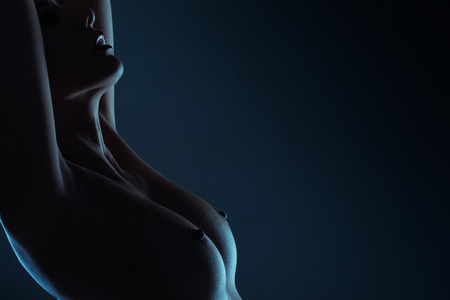 Dark atmospheric portrait of the bare breasts and nipples of a graceful young woman standing with her arms raised and copyspace