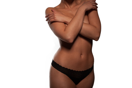 Torso of a beautiful topless woman in panties posing with her arms raised to accentuate the shape of her breasts and nipples, isolated on white photo