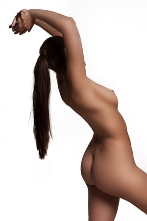Side view of the naked torso and curvaceous buttocks of a nude woman with her arms raised off frame isolated on white photo