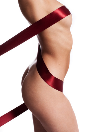 nude female buttocks: Red ribbon artistically wound around a naked female body concealing the nipple and accentuating the womans curves and sexy buttocks, side view of the torso isolated on white