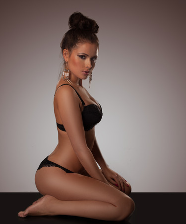 Elegant voluptuous woman in lingerie with gold earring and a neat bun kneeling on the floor looking seductively at the camera photo