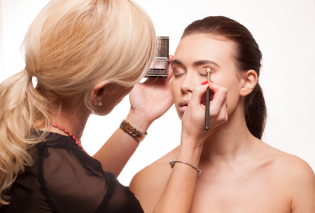 Beautician applying eye makeup to an attractive young model with bare shoulders as she prepares for a photo shoot, isolated on white photo